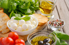 Italian food ingredients – mozzarella, tomatoes, basil and olive oil on rustic wooden background Stock Photo