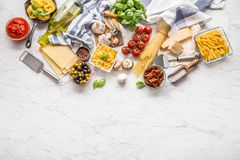 Italian food ingredients pasta olive oil parmesan cheese basil g. Arlic mushrooms tomatoes olives on marble board royalty free stock image