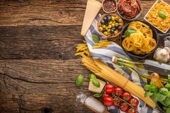 Italian food ingredients pasta olive oil parmesan cheese basil g. Arlic mushrooms tomatoes olives on wooden table stock photography