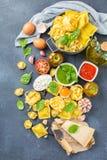 Italian food and ingredients, ravioli pasta tortellini pesto tomato sauce. Assortment of italian food and ingredients, ravioli with ricotta and spinach pasta Royalty Free Stock Photography