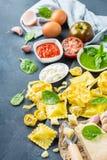 Italian food and ingredients, ravioli pasta tortellini pesto tomato sauce. Assortment of italian food and ingredients, ravioli with ricotta and spinach pasta Stock Image
