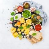 Italian food and ingredients, ravioli pasta tortellini pesto tomato sauce. Assortment of italian food and ingredients, ravioli with ricotta and spinach pasta Stock Photo
