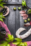 Italian food lifestyle background with salami, wine,olives and grape leaves on dark wooden background, top view Royalty Free Stock Images