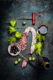 Italian food lifestyle with salami, red wine, grape leaves and olives on dark background, top view. Royalty Free Stock Images