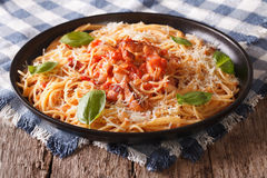 Italian food: pasta with Amatriciana Sauce  and basil close-up. Royalty Free Stock Photo