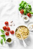 Italian food pasta background with copy space on white background, top view. Basil, whole grain spaghetti, cherry tomatoes, olive Royalty Free Stock Images