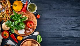 Italian food. Pasta basil tomato and olive oil on wooden black blackboard rustic style top view wiith copyspace. Royalty Free Stock Photos