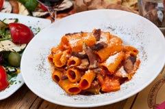 Italian food pasta dish. Served pasta dish with tomato sauce and cheese at italian restaurant Royalty Free Stock Photo