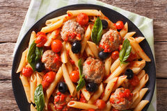Italian Food: Pasta with meatballs, olives and tomato sauce clos Royalty Free Stock Photos