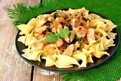 Italian food with pasta tagliatelle,sun dried tomatoes,basil and chicken meat on green cloth on wooden background Stock Photos