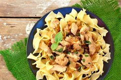 Italian food with pasta tagliatelle,sun dried tomatoes,basil and chicken meat on green cloth on wooden background Royalty Free Stock Photo
