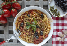 Italian food: pasta with tomatoes, olives and capers, called put Royalty Free Stock Image