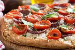 Italian food - pizza with salami and tomatoes, selective focus Stock Photography