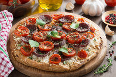 Italian food - pizza with salami and tomatoes on wooden board Royalty Free Stock Photography