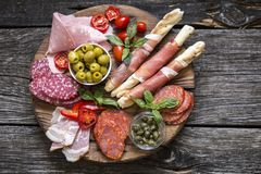 Italian food, prosciutto, grissini, smoked sausage, ham, olives, capers, sun-dried tomatoes on wooden background. Italian food, prosciutto, grissini, smoked stock photo