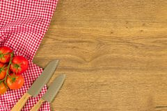 Italian food and raw ingredients on wooden background. Top view. Italian food ingredients and checkered napkin on wooden table. Top view with space for your text Stock Photography