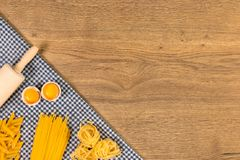 Italian food and raw ingredients on wooden background. Top view. Italian food ingredients and checkered napkin on wooden table. Top view with space for your text Royalty Free Stock Images