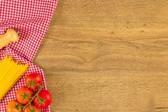 Italian food and raw ingredients on wooden background. Top view. Italian food ingredients and checkered napkin on wooden table. Top view with space for your text Royalty Free Stock Photos