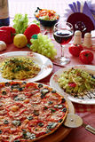 Italian food setting with pizza, pasta and wine