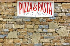 Italian Food Sign on Old Stone Wall Stock Images