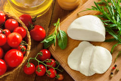 Italian food. Sliced mozzarella, tomatoes and arugula on table, top view Stock Images