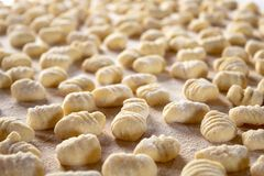 Italian food speciality: hand made potato gnocchi on a wooden board, ready to be cooked. Home made and hand rolled on a fork. Close up, selective focus stock photo