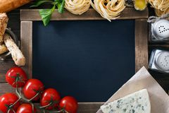 Italian food on vintage wood background with chalkboard Royalty Free Stock Photo