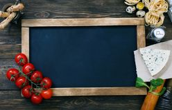 Italian food on vintage wood background with chalkboard Stock Images