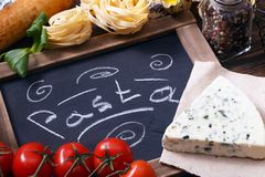 Italian food on vintage wood background with chalkboard Royalty Free Stock Images