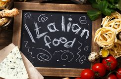 Italian food on vintage wood background with chalkboard Stock Photos