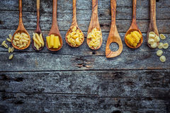 Italian foods concept and menu design. Various kind of Pasta Far. Falle, Pasta A Riso, Orecchiette Pugliesi, Gnocco Sardo and Farfalle in wooden spoons setup on Royalty Free Stock Image