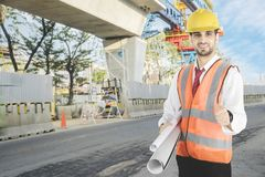 Italian foreman is showing a thumb up. Italian foreman is carrying blueprints while showing thumb up at the construction site stock images