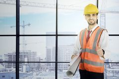 Italian foreman with blueprints and OK sign. Italian foreman is showing OK sign while standing in the office with the construction site in the window stock image