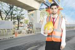 Italian foreman stands at the construction site. Italian foreman smiling at the camera while holding his yellow helmet and standing in the construction site royalty free stock image