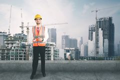 Italian foreman uses tablet on the rooftop. Picture of Italian foreman using a digital tablet while standing on the rooftop with construction site background stock photos