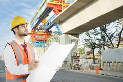 Italian foreman working with a blueprints at outdoor. Picture of Italian foreman checking in the construction site while working with a blueprint royalty free stock photos