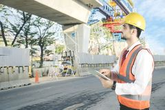 Italian foreman working with a tablet at outdoor. Italian foreman working with a digital tablet while checking construction site, Shot at outdoor stock photography