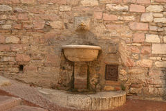 Italian fountain. In front of natural stone wall Stock Image