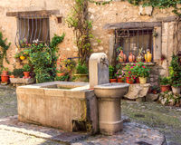 Italian fountian. With flowers and old house Stock Photography