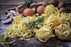 Italian fresh pasta. Fresh egg tagliatelle italian homemade pasta on wooden board Royalty Free Stock Photography