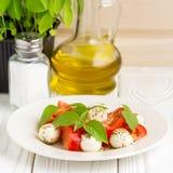 Italian fresh tomato Caprese salad, mozzarella, Basil. Italian fresh tomato Caprese salad, mozzarella and Basil, delicious light summer snack Royalty Free Stock Photo