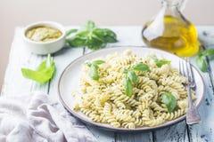Italian fusilli pasta with pesto. Italian fusilli pasta with fresh homemade pesto sauce on a plate over white wooden background stock image