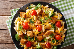 Italian fusilli pasta with pork, broccoli, tomatoes and cheese c. Heddar close-up on the table. horizontal view from above stock photo