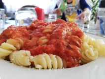 Italian fusilli pasta with tomato sauce close up. Having lunch or dinner with fresh italian fusilli pasta with tomato sauce. Pasta in a plate on a table. Woman royalty free stock photos