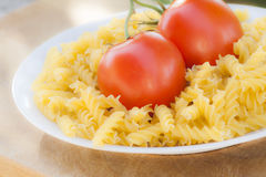 Italian fusilli pasta with tomatoes. A plate of Italian fusilli pasta with tomatoes (raw food view: just ingredients to be cooked Royalty Free Stock Photo