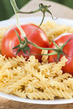 Italian fusilli pasta with tomatoes. A plate of Italian fusilli pasta with tomatoes (raw food view: just ingredients to be cooked Royalty Free Stock Images