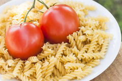 Italian fusilli pasta with tomatoes. A plate of Italian fusilli pasta with tomatoes (raw food view: just ingredients to be cooked Stock Photos