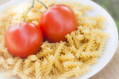 Italian fusilli pasta with tomatoes. A plate of Italian fusilli pasta with tomatoes (raw food view: just ingredients to be cooked Royalty Free Stock Photos