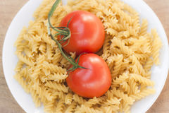 Italian fusilli pasta with tomatoes. A plate of Italian fusilli pasta with tomatoes (raw food view: just ingredients to be cooked Royalty Free Stock Image