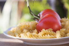 Italian fusilli pasta with tomatoes. A plate of Italian fusilli pasta with tomatoes (raw food view: just ingredients to be cooked Stock Photography